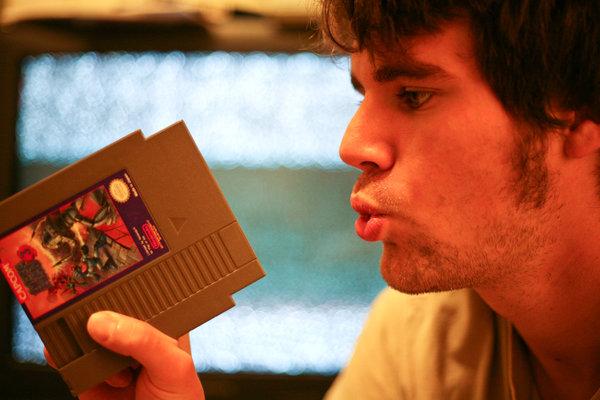 Парень продувает картридж для NES.